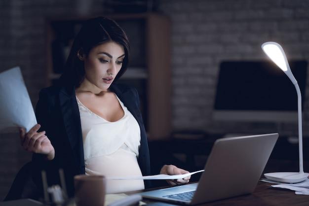 Müde schwangere geschäftsfrau, die im büro arbeitet
