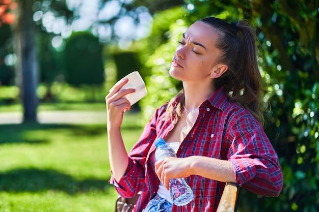 Müde schwitzende frau, die im schatten ruht, während in einem park bei heißem wetter