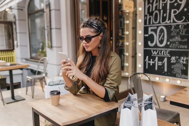 Müde shopaholic-frau, die im herbstcafé im straßencafé kühlt