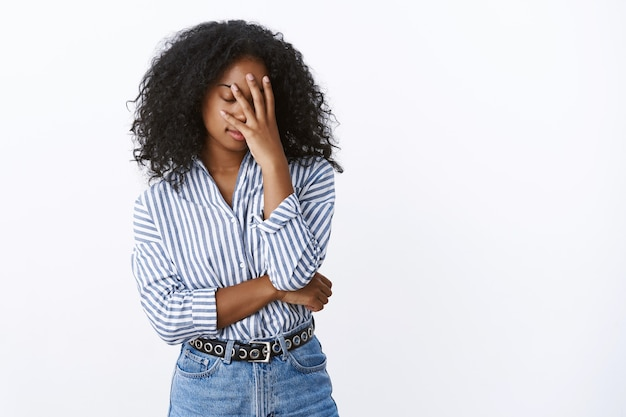 Müde snobistisch gutaussehende stylische afroamerikanerin lockige frau gesichtpalm enge augen belästigt dumm dummer kollege hat einen fehler gemacht stehend erschöpft sauer genervt, will nach hause gehen