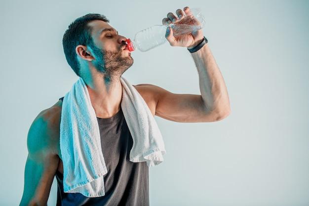 Müde sportler trinkwasser aus der flasche nach dem training. junger bärtiger europäischer mann mit geschlossenen augen und handtuch. person trägt sportuniform. auf türkisfarbenem hintergrund isoliert. studioshooting