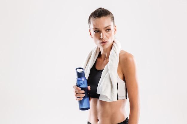 Müde sportlerin mit handtuch am hals hält wasserflasche