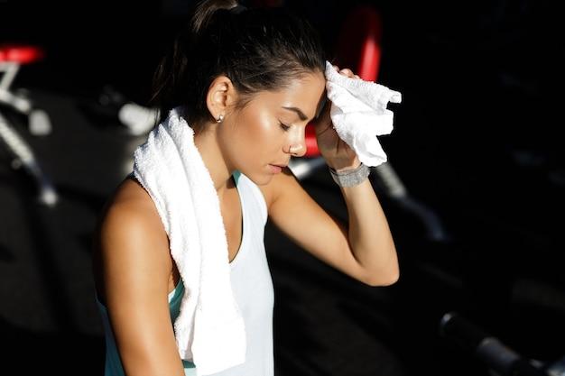 Müde sportlerin mit handtuch mit geschlossenen augen nach dem training im fitnessstudio