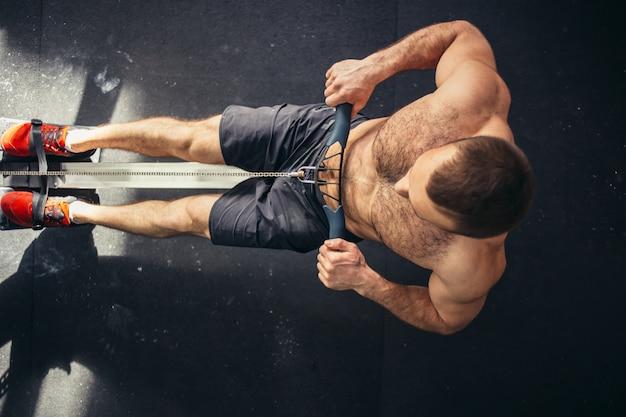 Müde sportliche männliche workouts auf krafttrainingsgerät in einem fitnessclub