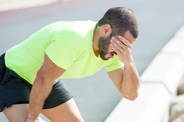 Müde sportlicher mann entspannend und bedecken gesicht
