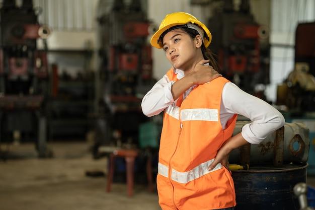 Müde stress-arbeiterinnen nackenschmerzen, die in der schwerindustrie-fabrik arbeiten, gesundheitsproblem asiatisches arbeitskonzept.