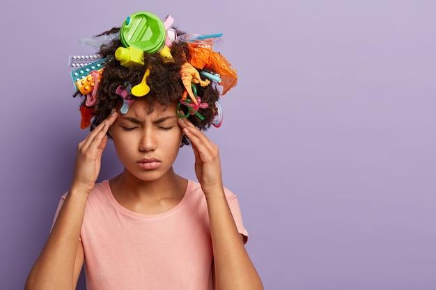 Müde stressige frau, die mit müll in ihren haaren aufwirft