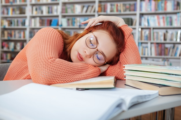 Müde studentin, die nach dem studium in der bibliothek auf ihrem schreibtisch schläft