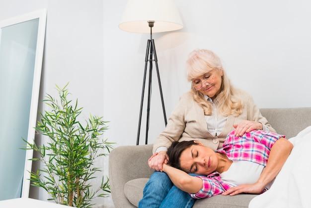 Müde tochter, die auf dem schoss ihrer mutter sitzt, die über dem sofa sitzt