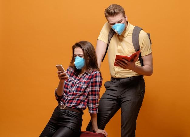 Müde touristen, reisender mann und frau in medizinischen masken auf einem gelben orange hintergrund, coronavirus-pandemie, geschlossene grenzländer, großer koffer