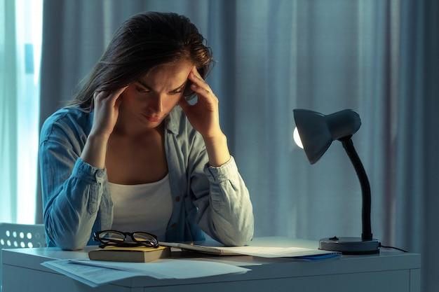 Müde traurige überarbeitete geschäftsfrau, die müdigkeit und kopfschmerzen fühlt, während sie spät in der nacht zu hause arbeitet. lange und sitzende arbeit
