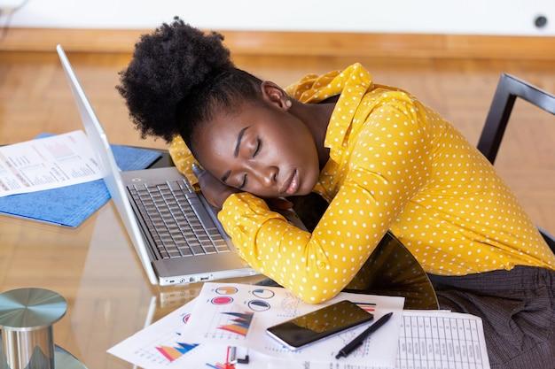 Müde überarbeitete frau, die stillsteht, während sie arbeitet, anmerkungen schreibend. überarbeitete und müde geschäftsfrau, die zu hause über einem laptop in einem schreibtisch schläft. müde geschäftsfrau