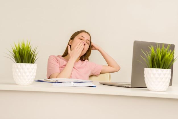 Müde überarbeitete junge praktikantin, die mit einem laptop in einem büro arbeitet