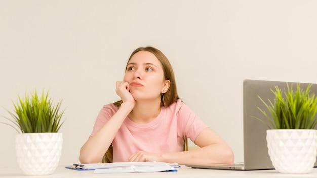 Müde überarbeitete junge praktikantin, die mit einem laptop in einem bürobild arbeitet