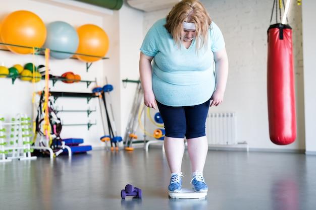 Müde übergewichtige frau im fitnessstudio