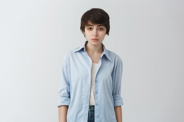 Müde und düstere junge nicht-binäre person, die mit traurigem gesicht schaut