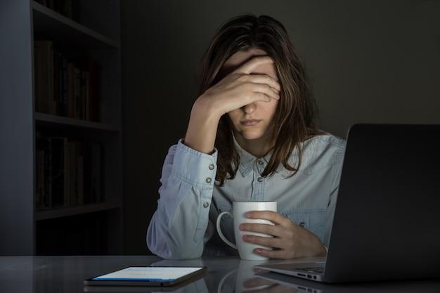 Müde und enttäuschte weibliche person am home-office-arbeitsplatz spät in der nacht