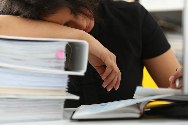 Müde und erschöpfte frau haben viel arbeit mit dokumenten beim einschlafen