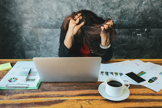 Müde und kopfschmerzengeschäftsfrau im büro unter verwendung des laptops und analysieren von investitionsdiagrammen auf dokumentenpapier