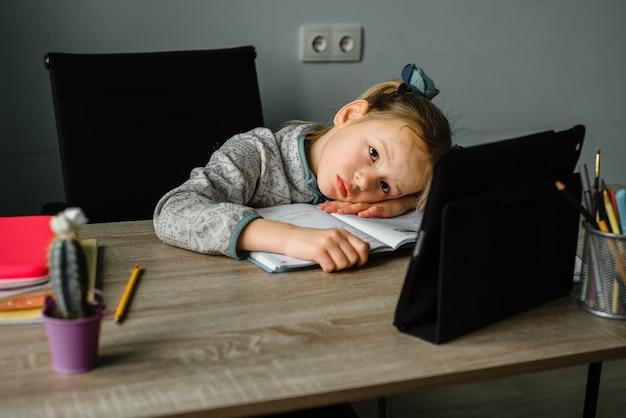 Müde und schläfriges kleines mädchen, das online-unterricht zu hause hat