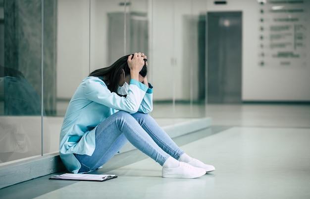 Müde und unglückliche junge ärztin in sicherheitsmaske in stress nach fehlgeschlagener arbeit