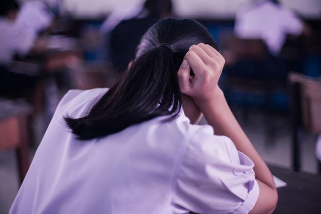 Müde uniformierte schüler schlafen in einem prüfungstest im klassenzimmer mit stress