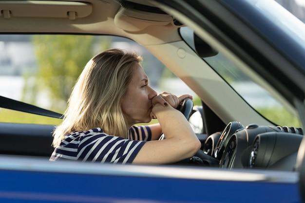 Müde, unwohle frau im auto auf dem fahrersitz, erschöpfte frau, die vor dem missbrauch des ehemannes davongelaufen ist