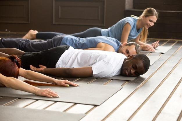 Müde verschiedene leute, die auf matten nach dem yoga sich ausdehnen, der trai ausdehnt