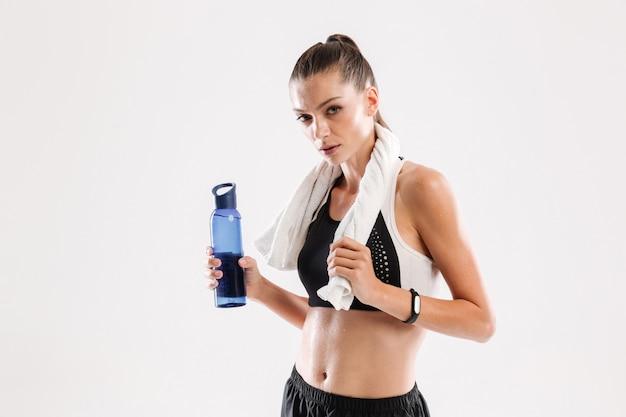 Müde verschwitzte fitnessfrau mit handtuch am hals