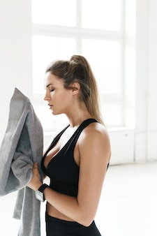 Müde verschwitzte frau mit handtuch nach dem fitnesstraining im fitnessstudio