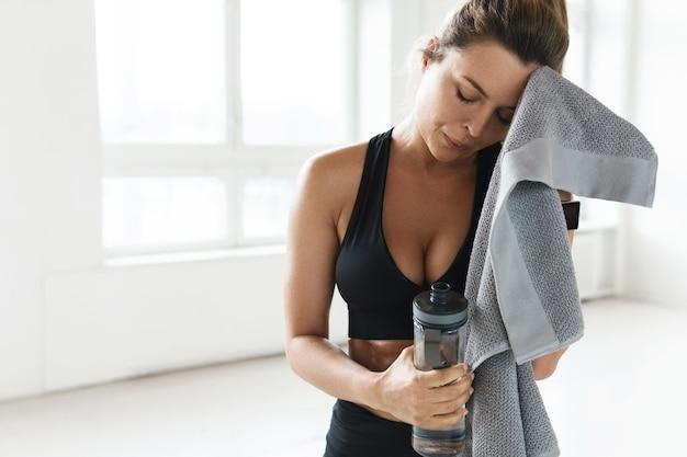 Müde verschwitzte frau trinkt wasser nach hartem fitnesstraining im fitnessstudio
