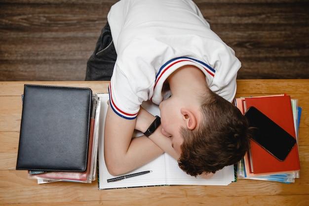 Müde vom unterricht schläft ein teenager zu hause für lehrbücher am tisch