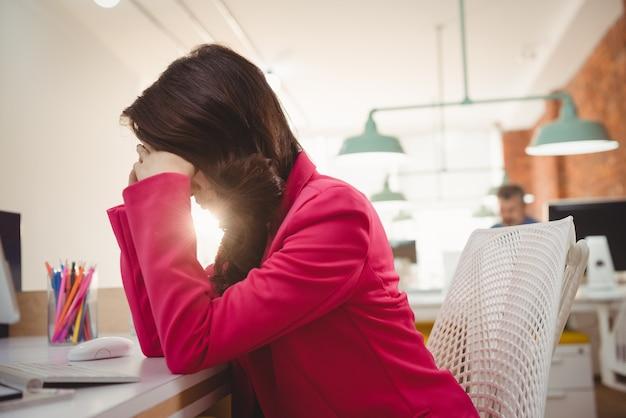 Müde weibliche führungskraft, die mit den händen auf der stirn am schreibtisch sitzt