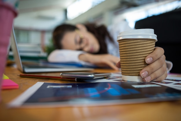 Müde weibliche grafikdesignerin, die einwegbecher beim schlafen auf schreibtisch hält