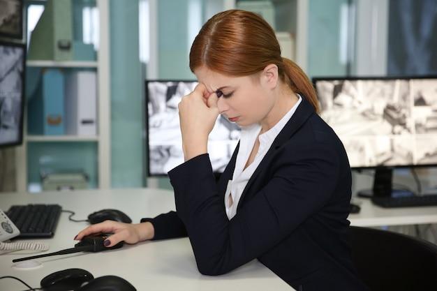 Müde weibliche sicherheitsbeamtin im überwachungsraum