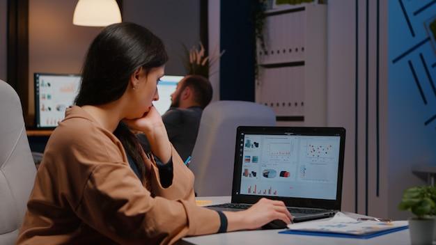 Müde workaholic-geschäftsfrau, die finanzstrategie auf laptop-computer eingibt