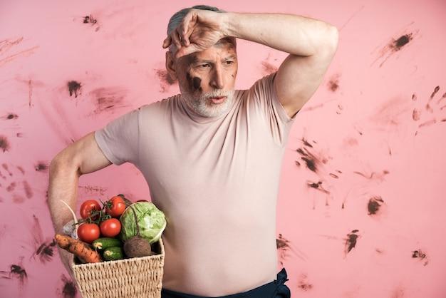 Müder älterer mann, der einen korb mit gemüse auf einer schmutzigen rosa wand hält