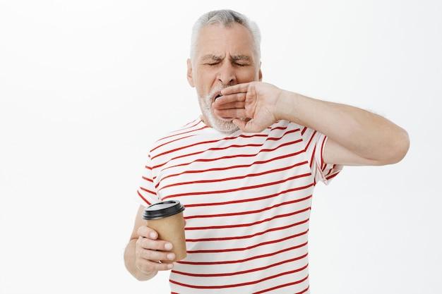 Müder älterer mann, der schläfrig gähnt und kaffee trinkt