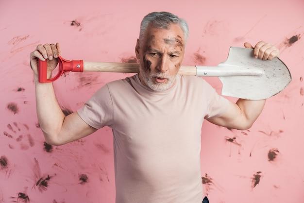 Müder älterer mann mit schmutzigem gesicht, das eine schaufel auf seinen schultern hält