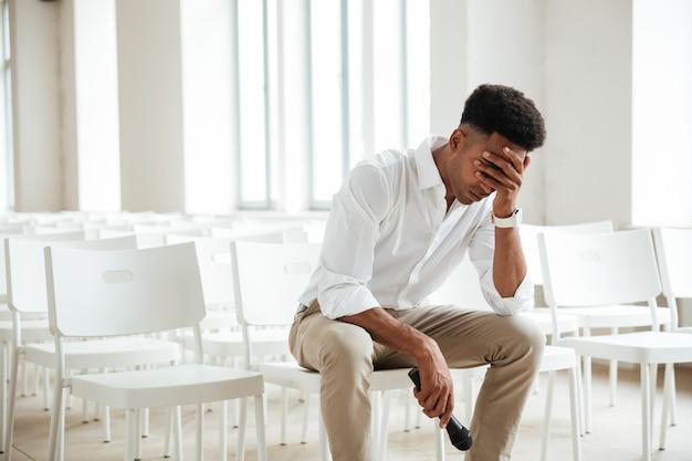 Müder afrikanischer mann, der im büro drinnen hält, das mikrofon hält.