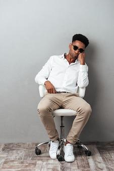 Müder afroamerikanischer mann in der sonnenbrille, die in einem stuhl sitzt