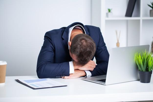 Müder angestellter, der am schreibtisch im firmenbüro arbeitet