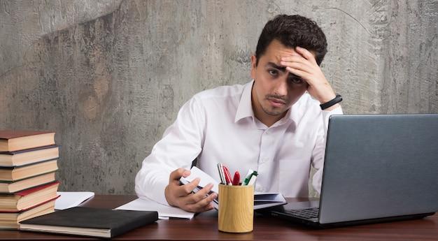 Müder angestellter, der am schreibtisch sitzt und auf papierbögen schaut. hochwertiges foto