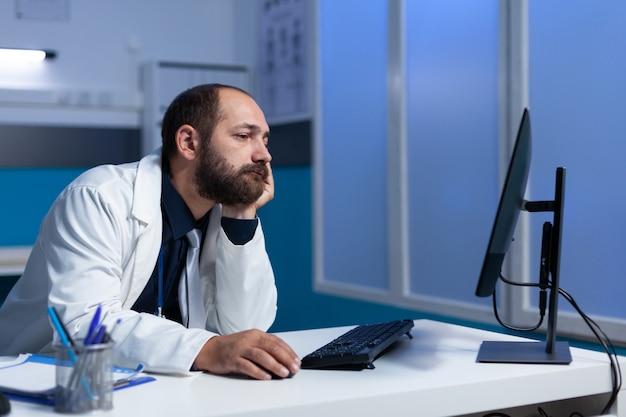 Müder arzt, der spät nachts mit monitor arbeitet