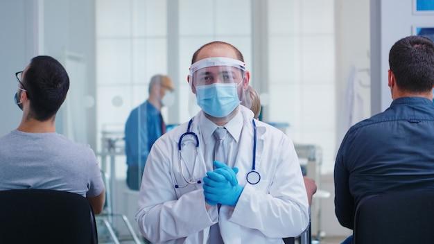 Müder arzt mit gesichtsmaske und visier gegen coronavirus im wartebereich des krankenhauses mit blick auf die kamera. älterer mann und krankenschwester im krankenhausuntersuchungsraum.