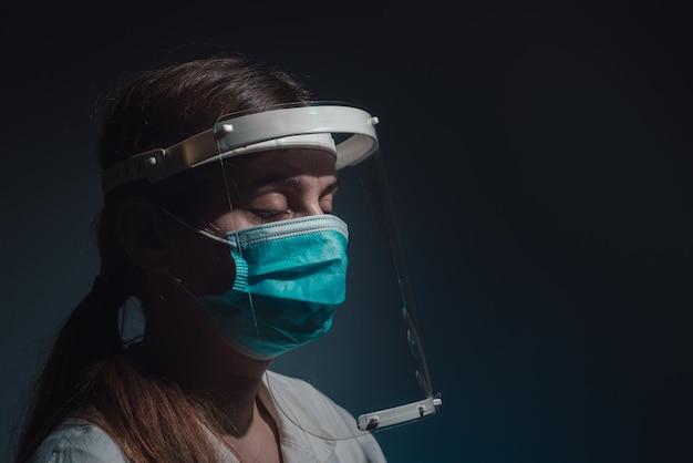 Müder arzt mit gesichtsschutz und maske auf dunklem hintergrund
