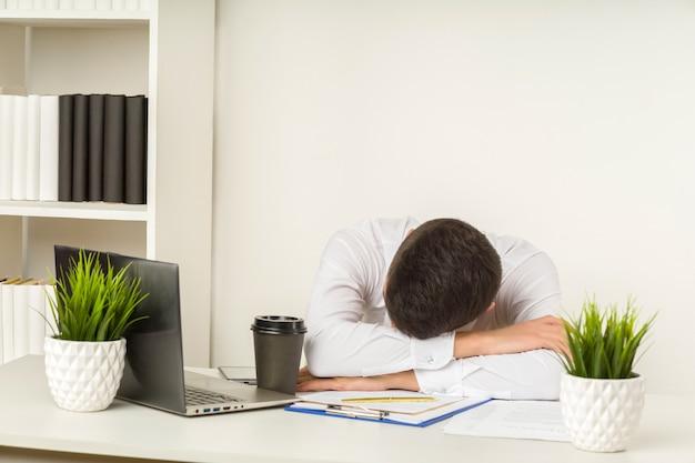 Müder asiatischer geschäftsmann, der im büro schläft