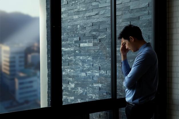 Müder asiatischer geschäftsmann, der in der seite des großen fensters im büro steht