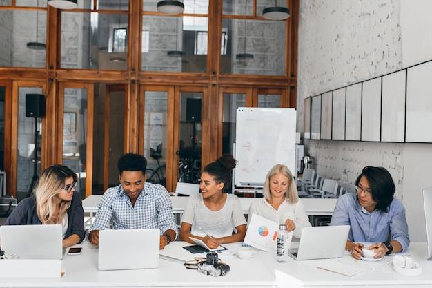 Müder asiatischer it-spezialist, der kaffee trinkt und kollegin beim arbeiten mit laptop beobachtet. innenporträt der jungen geschäftsleute, die zusammen am tisch im konferenzsaal sitzen.