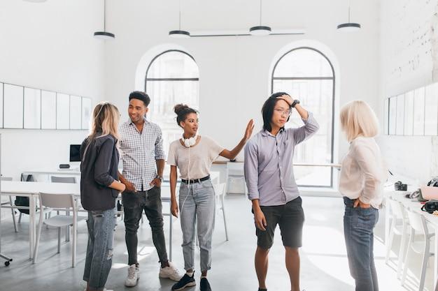 Müder asiatischer manager, der nach langer konferenz mit ausländischen partnern die stirn berührt. innenporträt von besorgten studenten, die auf testergebnis in der universität warten.